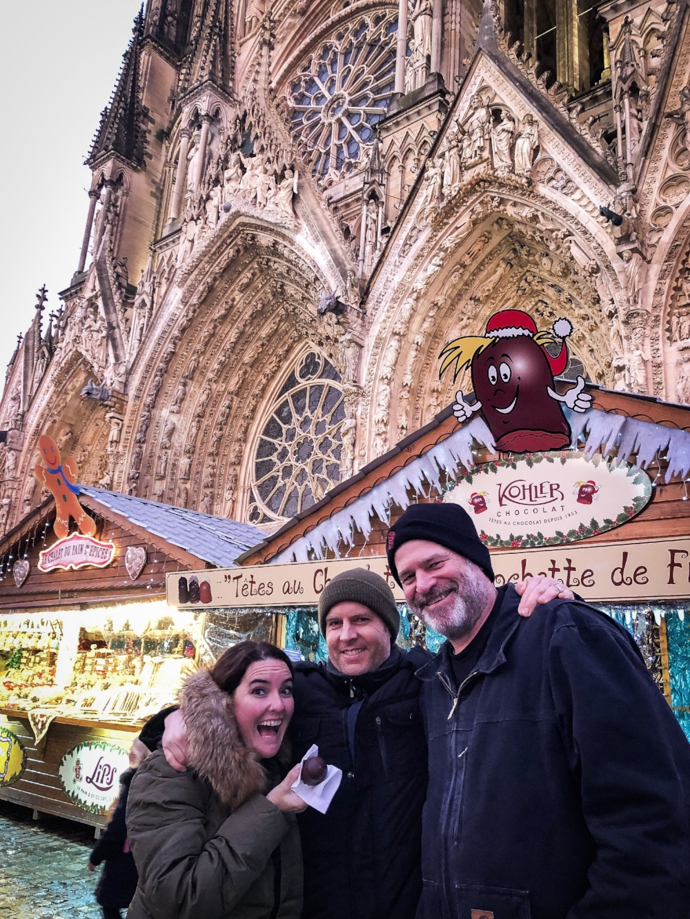 Claire, Justin, and Jeff enjoying chocolate at the Marche d'hiver in Reims, France, in the shadow of the Reims Cathedral