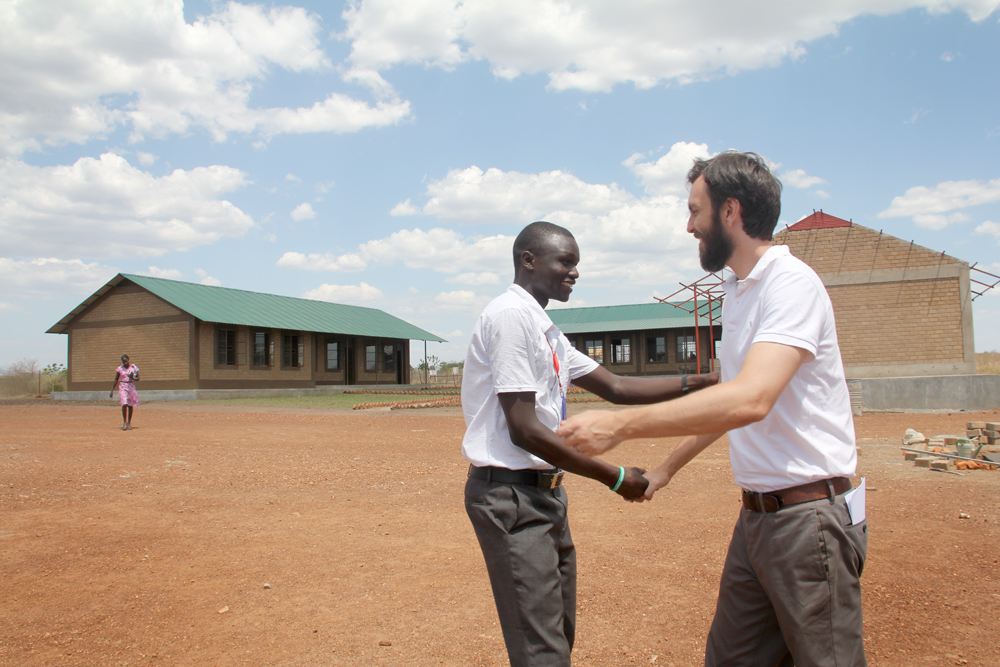 Eric greets Charles, a teacher at the school and an alumni of our Ugandan school