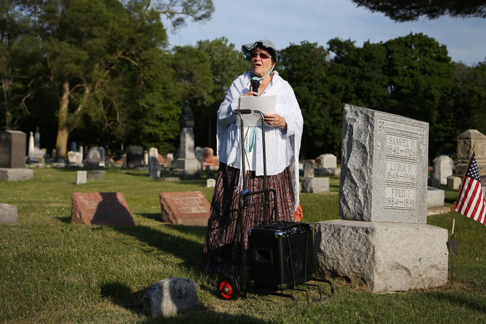 A woman reads a biography at Waterloo's cemetery walk