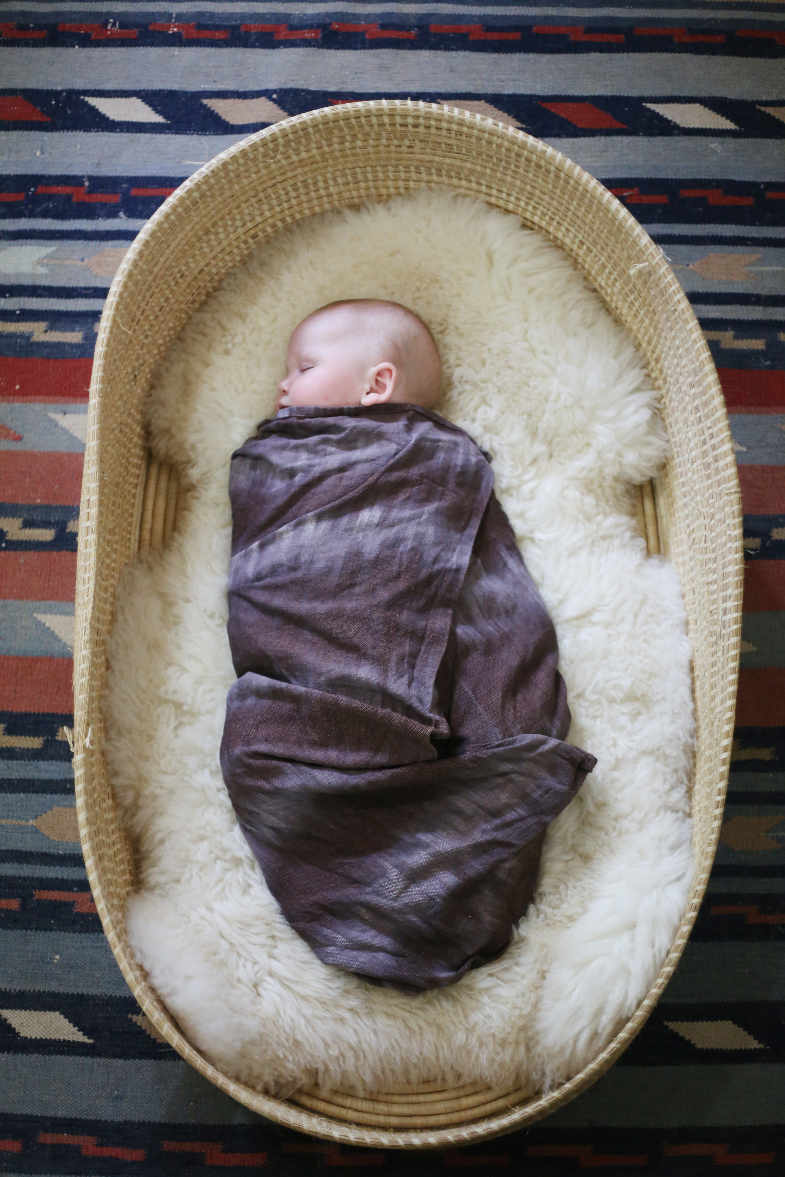 Moses basket woven in western Uganda and swaddle blanket handwoven from Ugandan cotton. Both are available at  Baby Lionheart.  Sheepskin rug from  Ecowool .