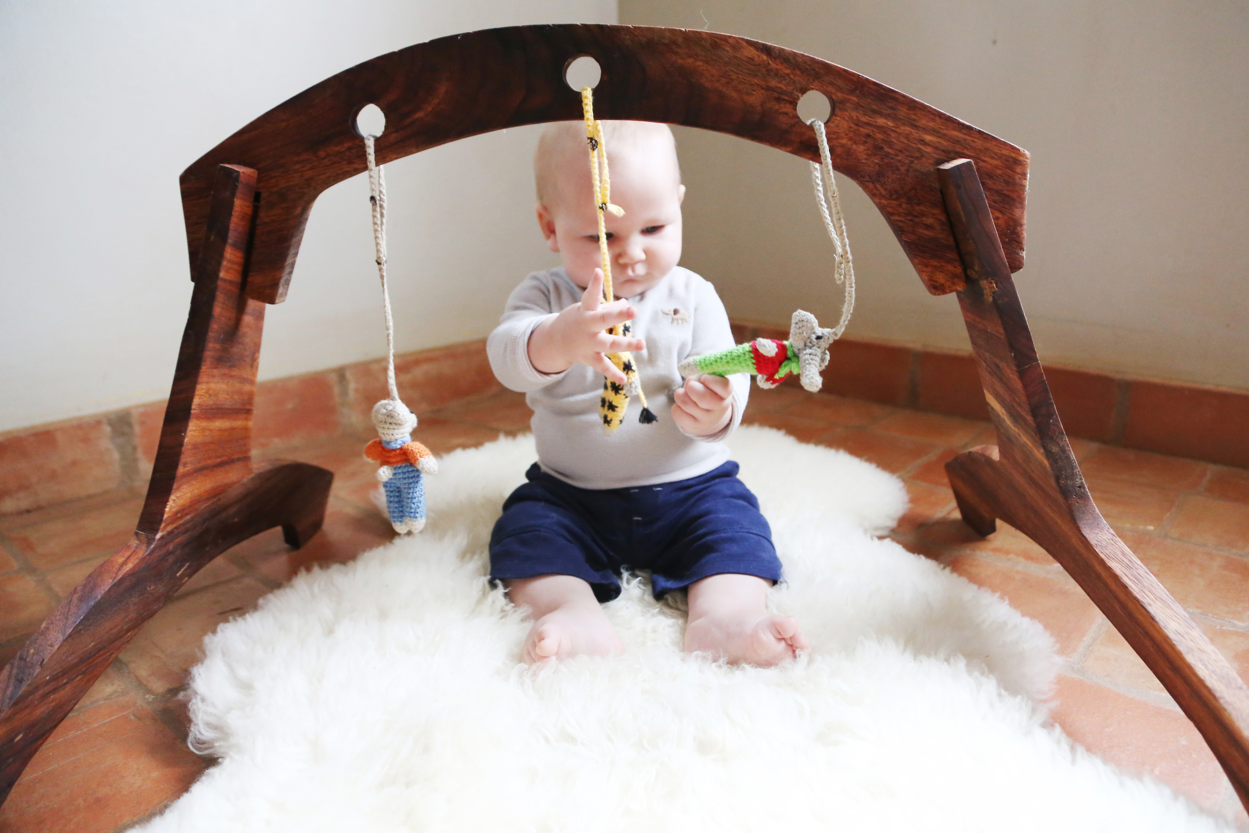 Activity gym handmade in Uganda, available at  Baby Lionheart .  Sheepskin from  Ecowool .