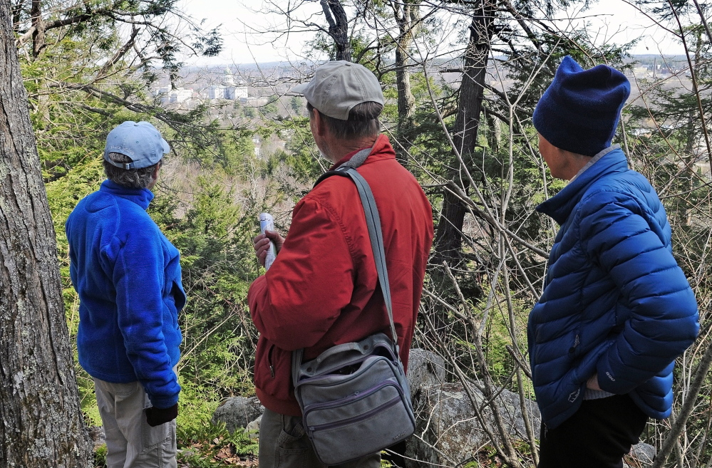 Hilltop view: City Councilor Dale McCormick, left, Brian Kent and Sue Bell look down from the summit onto the State House complex during a walking tour of Howard Hill on Friday in Augusta. The wooded hill is the backdrop to the State House.  Staff photo by Joe Phelan