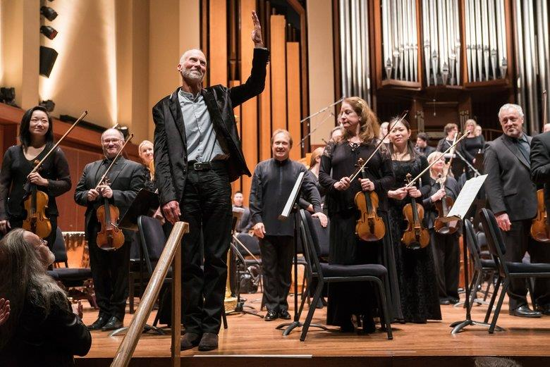 Adams, arm raised, takes a bow with the Seattle Symphony Orchestra.