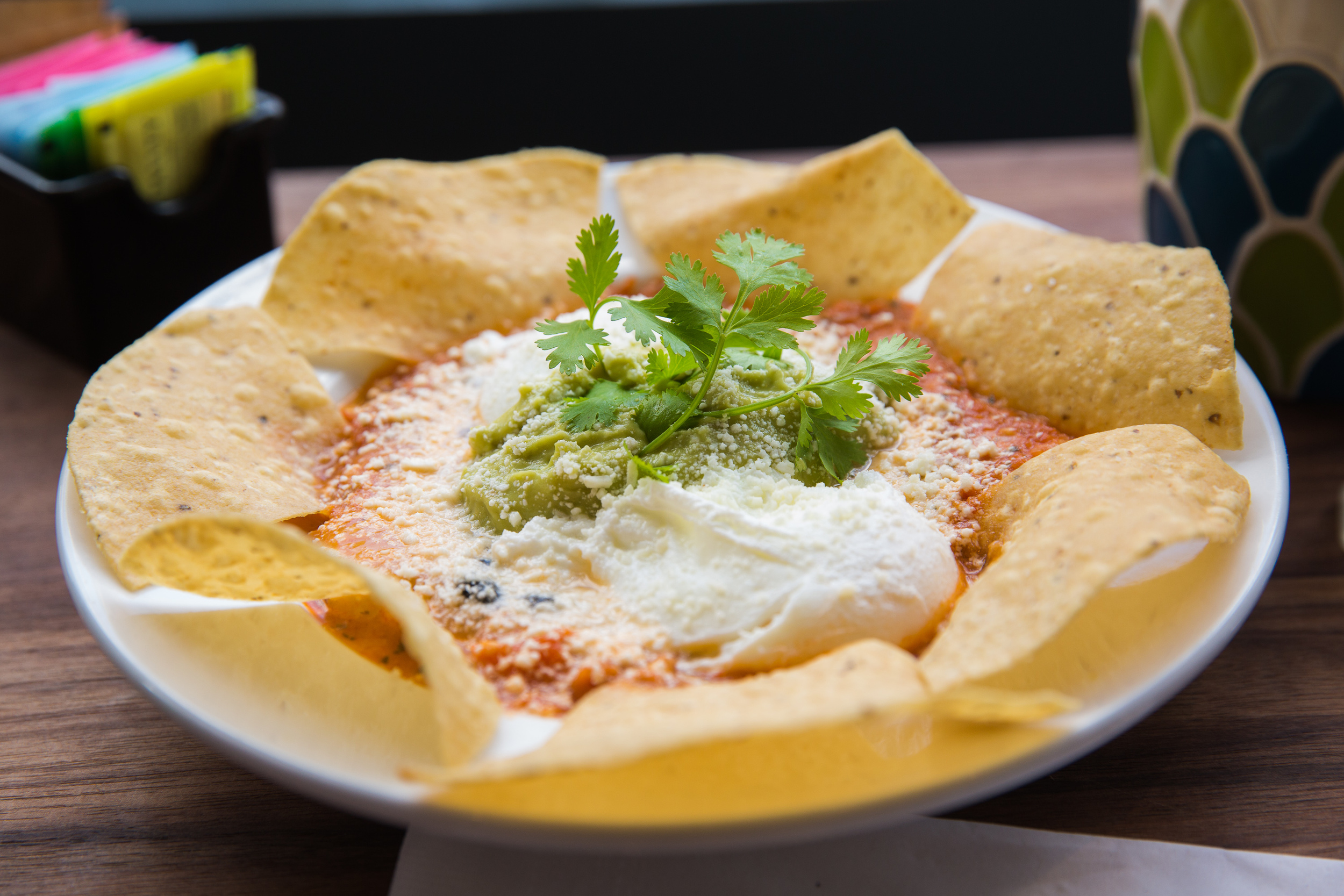 Huevos Rancheros - Poached Eggs, Salsa, Avocado Mousse, Black Beans, Cheddar & Cotila Cheese, Tortilla Chips