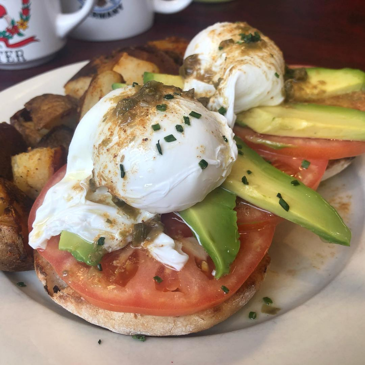 Capote Benedict - Poached eggs on top of Avocado & Tomato, topped with a drizzle of lemon-caper brown butter