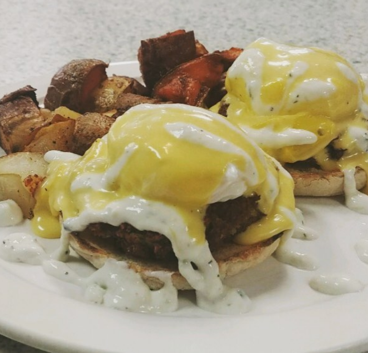 Falafel Benedict- Two patties, poached eggs, hollandaise, and tzatziki drizzle!