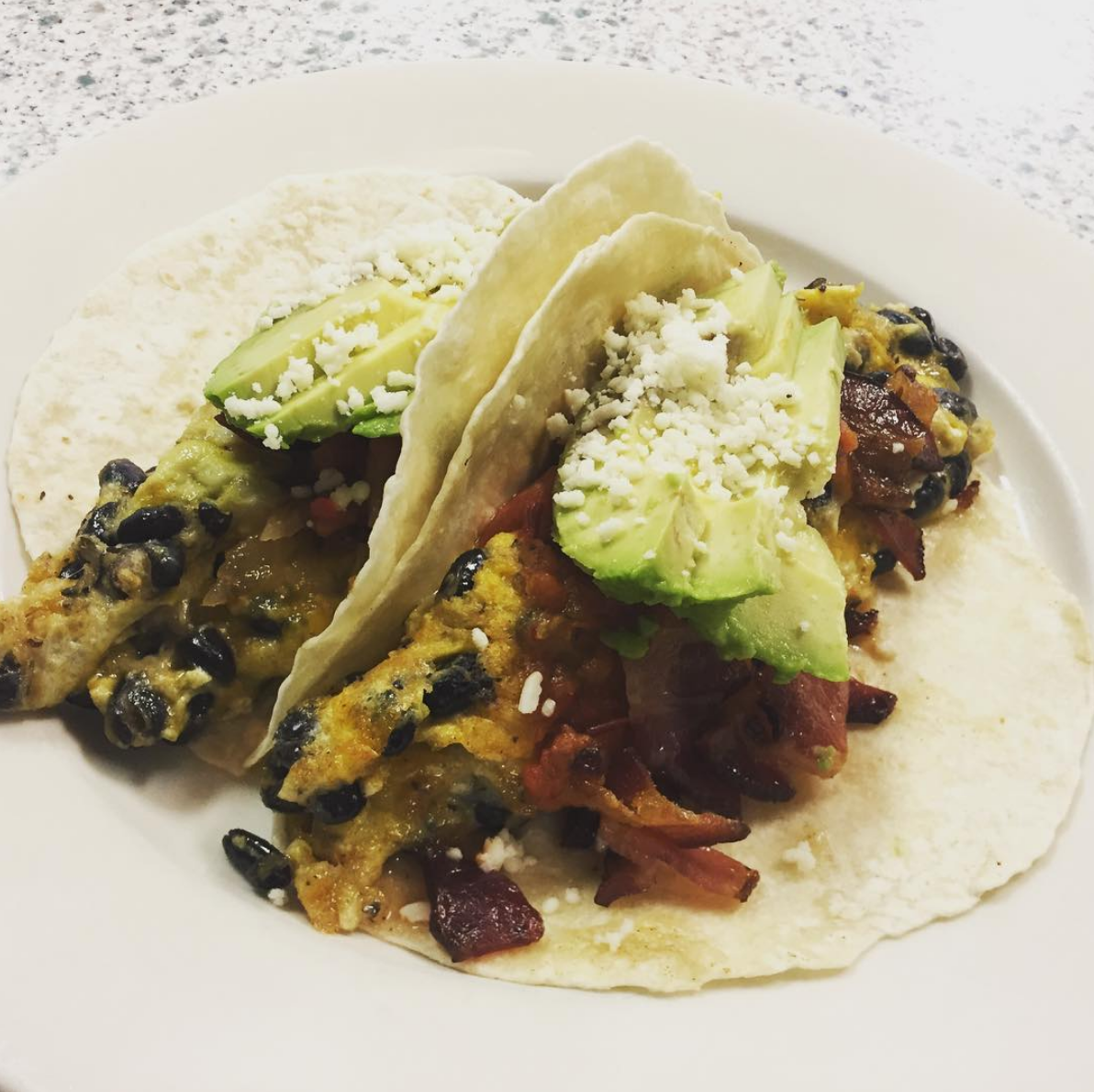 Breakfast Tacos - Corn tortillas filled with scrambled eggs, bacon, black beans, avocado, and cotija cheese