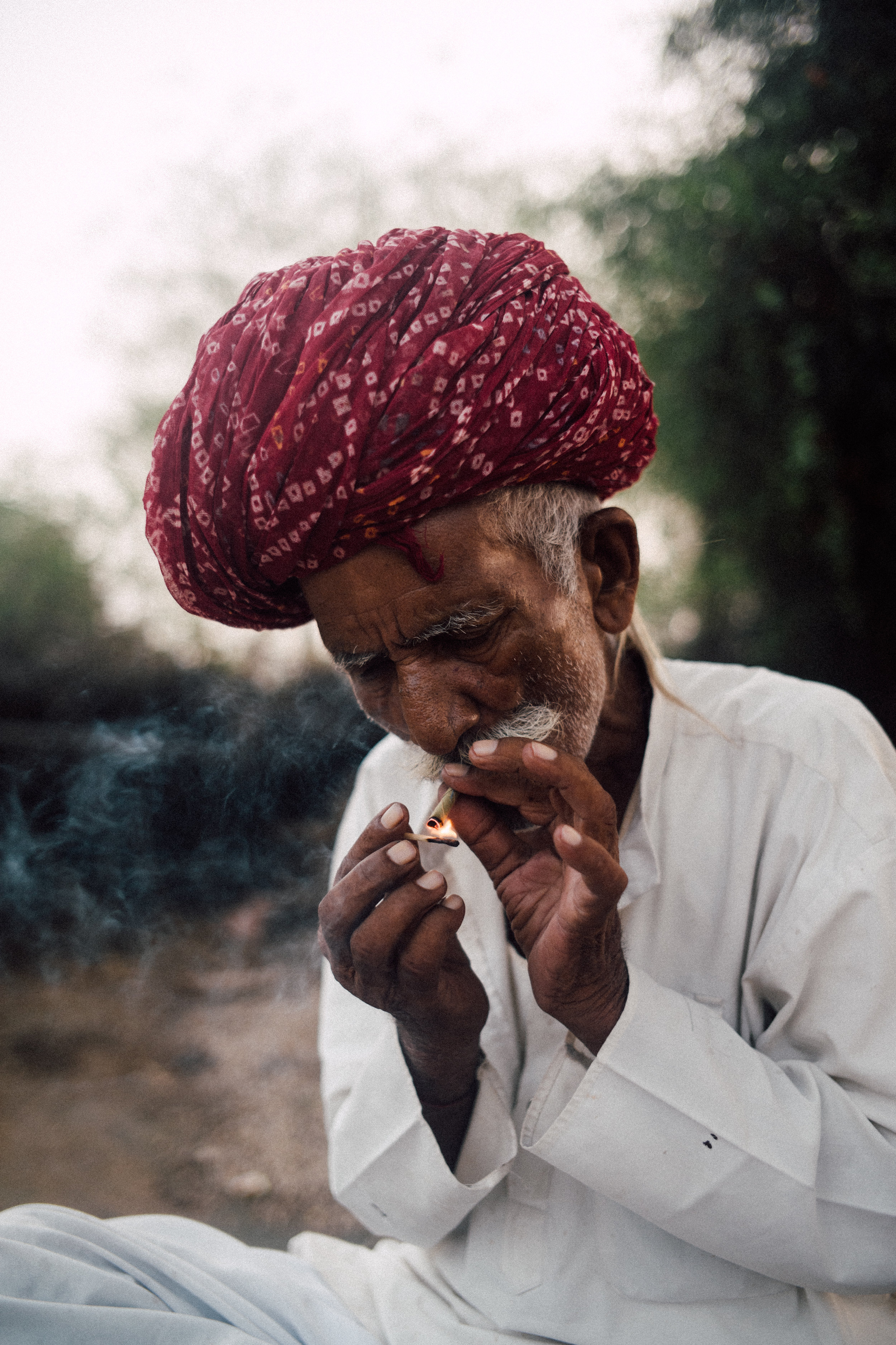 A Bishnoi village local roles and lights a cigarette as the sun behind him sets.