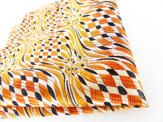Textured woven silk pocket square in a burnt orange flame geometric pattern.