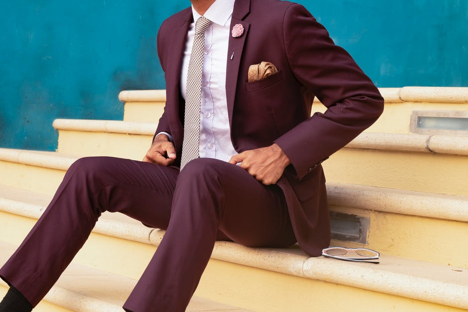Fashion forward merlot suit with floral lapel pin and poof fold pocket square. Beautiful colors that compliment each other, formal slant with lapel detail, lends itself to a poof pocket square style.