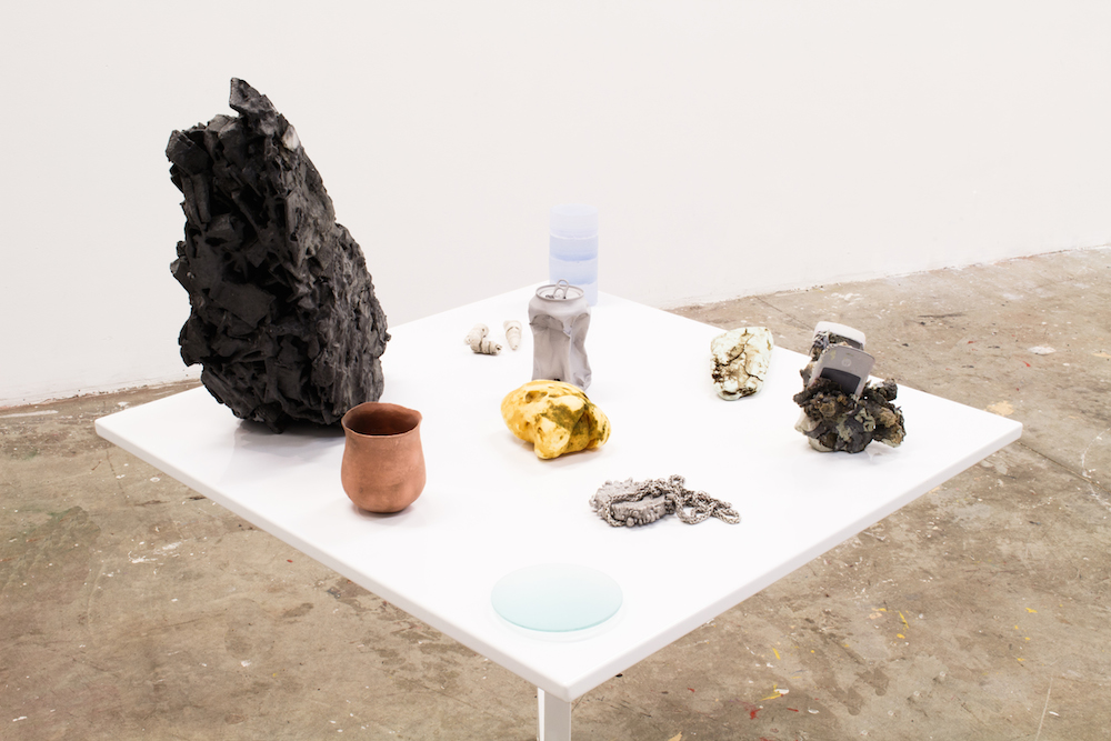 "On the Beach, 2015, 34""x34""x48"", plastic, resin, graphite, clay, sand, gold, aluminum, copper, chrome, nickel, glass, fossil gastropods, fossil shark teeth, foam, silica, wristwatch packaging, Motorola Razr, steel folding table"