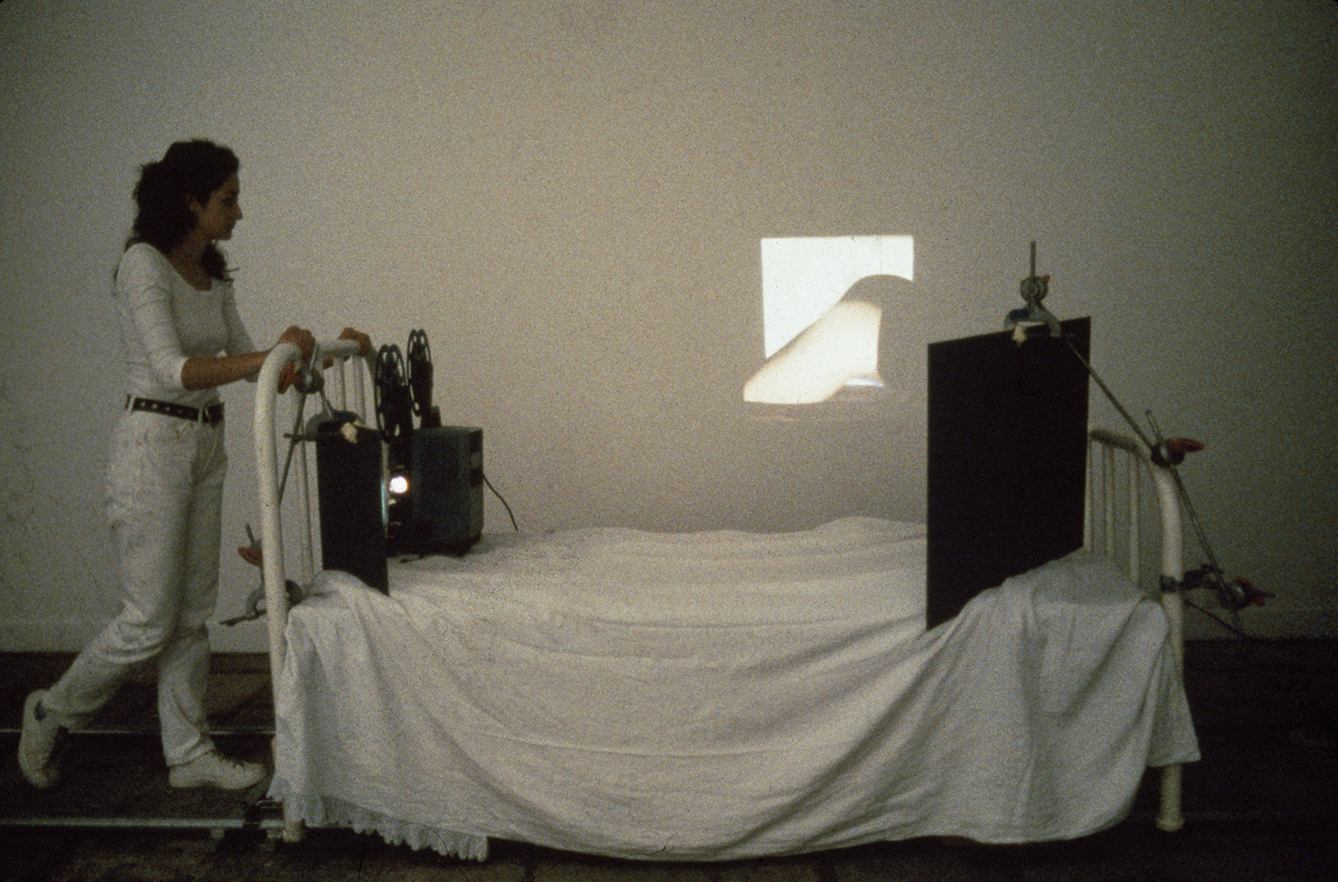 Eulalia Valldosera,  Embenatges - Bandages,  1992    16 mm film projector, film with soundtrack, 18'; individual hospital type bed; 2 mirrors; rails and dolly for traveling shots      Performance