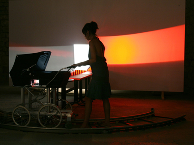 Eulalia Valldosera,  El periodo , 2006 Light participatory installation with baby pram.  Rails for a cinematographic travelling, trolley's support with wheels which fit on the rails; slide projector 250W without slide, lenses 70-120mm; baby trolley; 4 tables, 4 chairs, 4 stools; 28 glasses of red wine