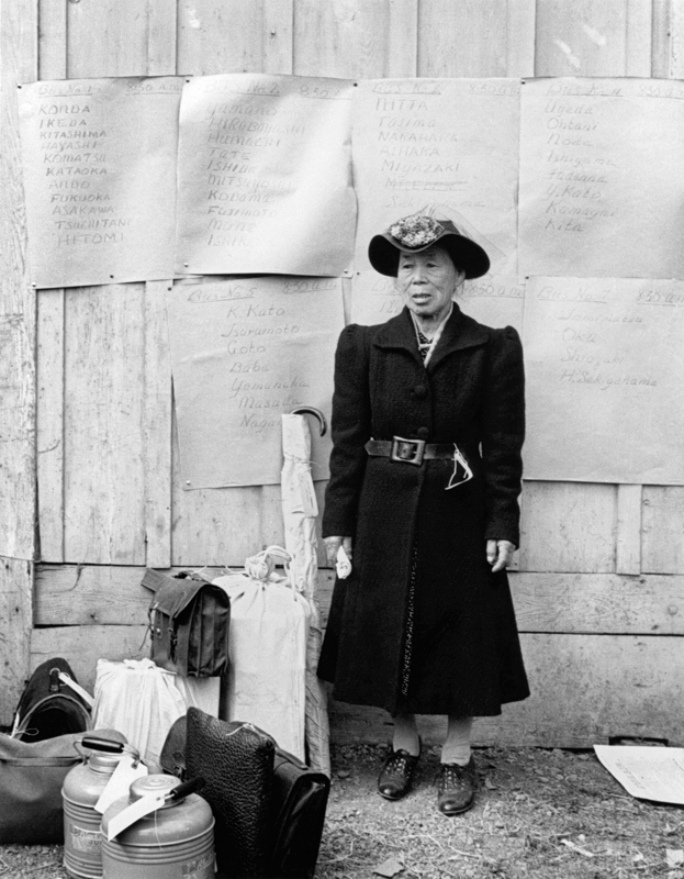 Dorothea Lange,  Japanese Woman in Flowered Hat in front of Posters with Names , California, 1942, cm 31x40, framed cm 55x55