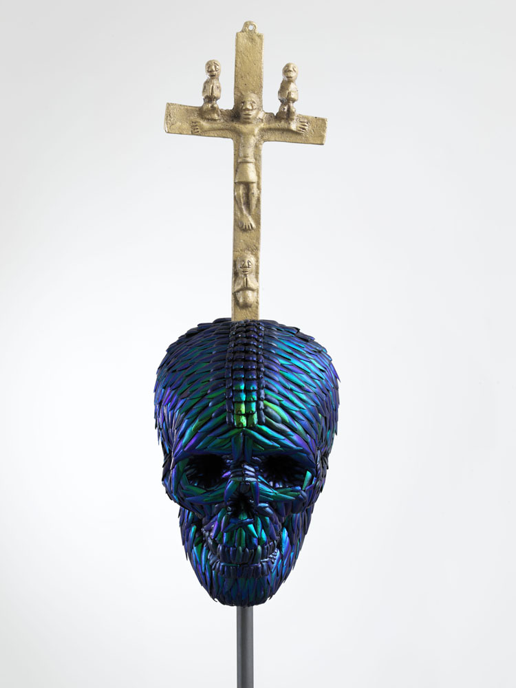 Skull with Bacongo Cross (Blue),  2018, mixture of jewel beetle wing-cases, polymers, metal, messing, H 89,7 x B 22 x D 22 cm, pedestal H 110 x W 35 x D 35 cm