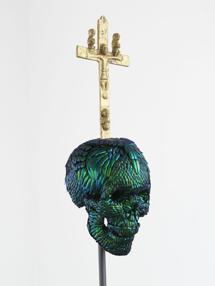 Skull with Bacongo Cross (Green) , 2018, mixture of jewel beetle wing-cases, polymers, metal, messing, H 89,9 x B 22 x D 22 cm, pedestal H 110 x W 35 x D 35 cm