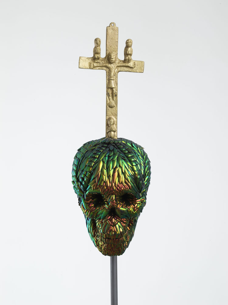 Skull with Bacongo Cross (Red) , 2018, mixture of jewel beetle wing-cases, polymers, metal, messing, H 89,9 x B 22 x D 22 cm, pedestal H 110 x W 35 x D 35 cm
