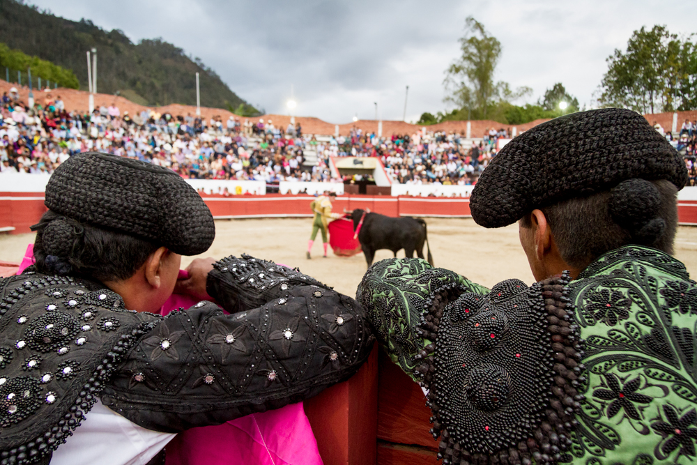 Two bull fighters look on as another confronts a bull in the ring.   In this series I photographed several young men who were training to become bull fighters in a small town called Choachí on the outskirts of Bogota, Colombia. They were committed to pursing this tradition, something they see as an art form, despite enduring an increasing amount of scrutiny from animal rights activists and an uncertain future.
