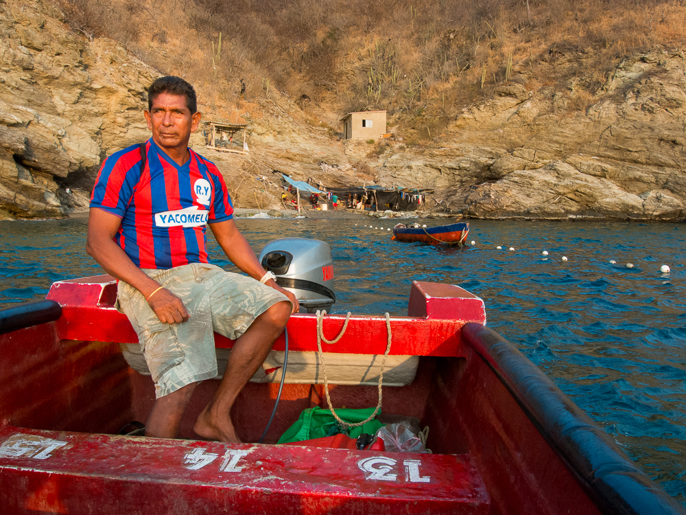 A man steers the boat away from the fishing cove, heading back to Taganga in the sunset.  In this series, I photographed the daily happenings of a group of fishermen in the small town of Taganga, on the northern coast of Colombia.They use a simple yet effective method, common of indigenous groups, that has been passed down through generations. Their connection to the sea and their commitment to this way of life persists despite the amassing threats of pollution and over-fishing by commercial enterprises.