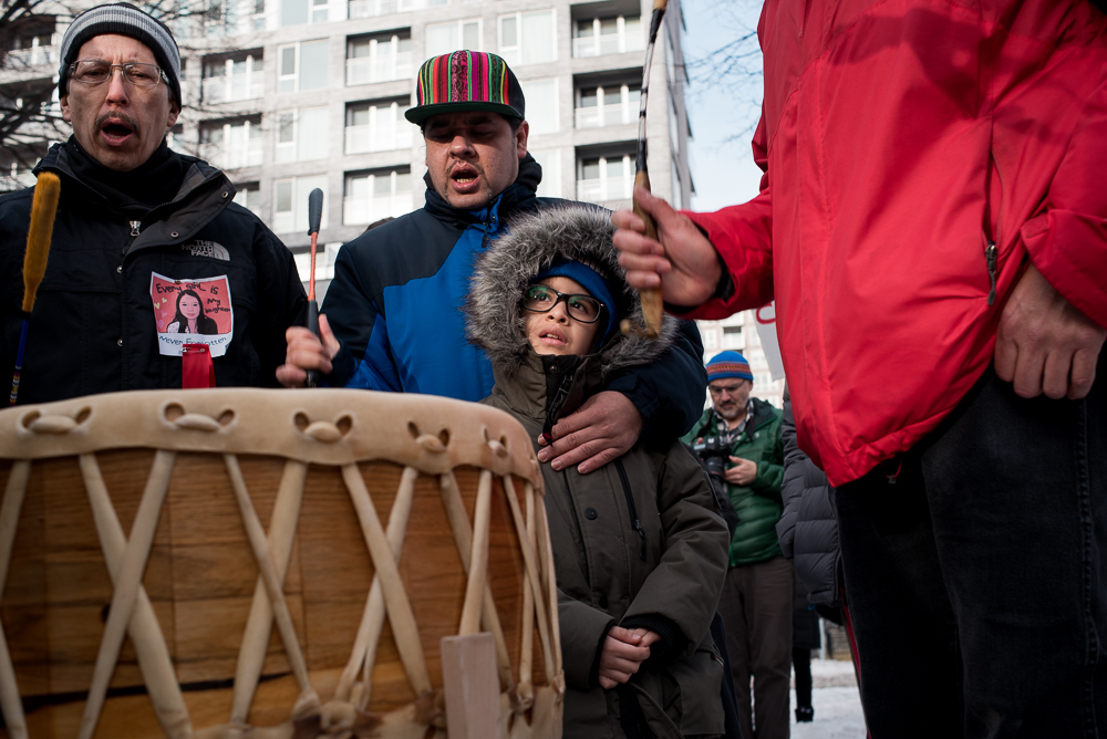MONTREAL, February 24, 2018. -- Samuel Medrano holds his son while drumming at the Tina Fontaine vigil. Fontaine's untimely death was partly responsible for launching the inquiry into missing and murdered Indgenous women.