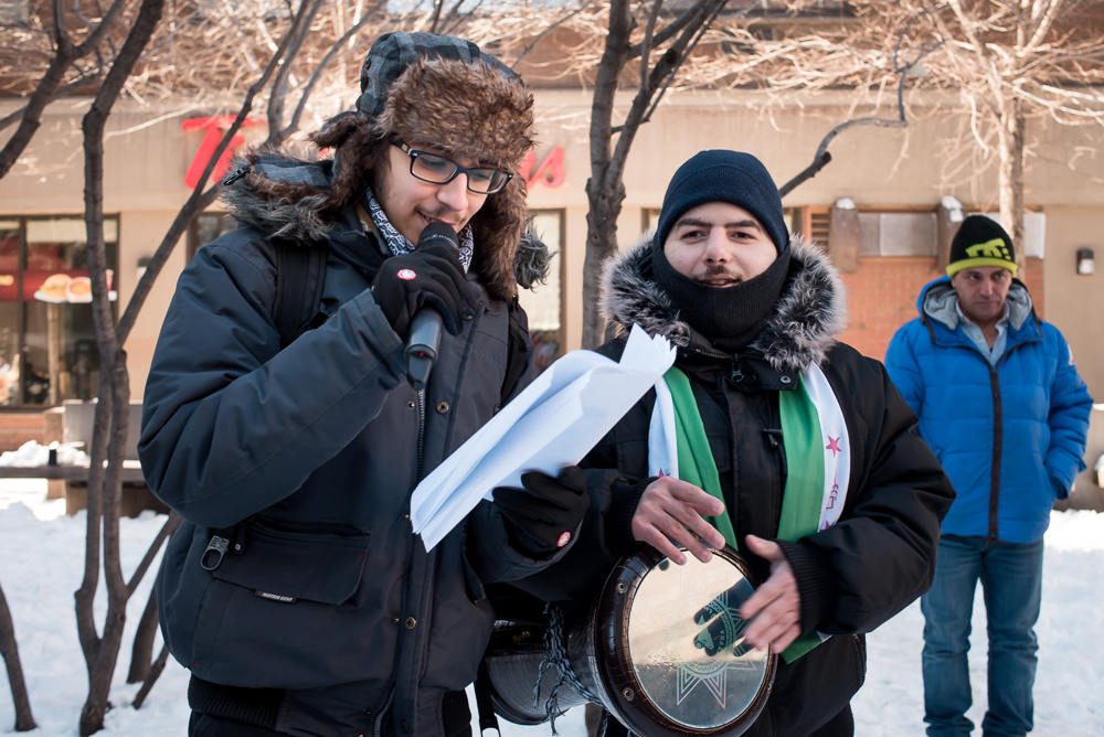 MONTREAL,March 18, 2018. -- Two young men lead protesters in song at the 7th anniversary of the Syrian uprising at Place Norman-Bethune, Montreal.