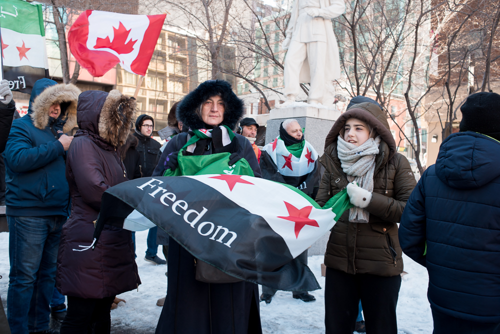 MONTREAL,March 18, 2018. -- Protesters wave flags at the 7th anniversary of the Syrian uprising at Place Norman-Bethune, Montreal. This uprising, which was initially peaceful led to a brutal civil war which still continues.