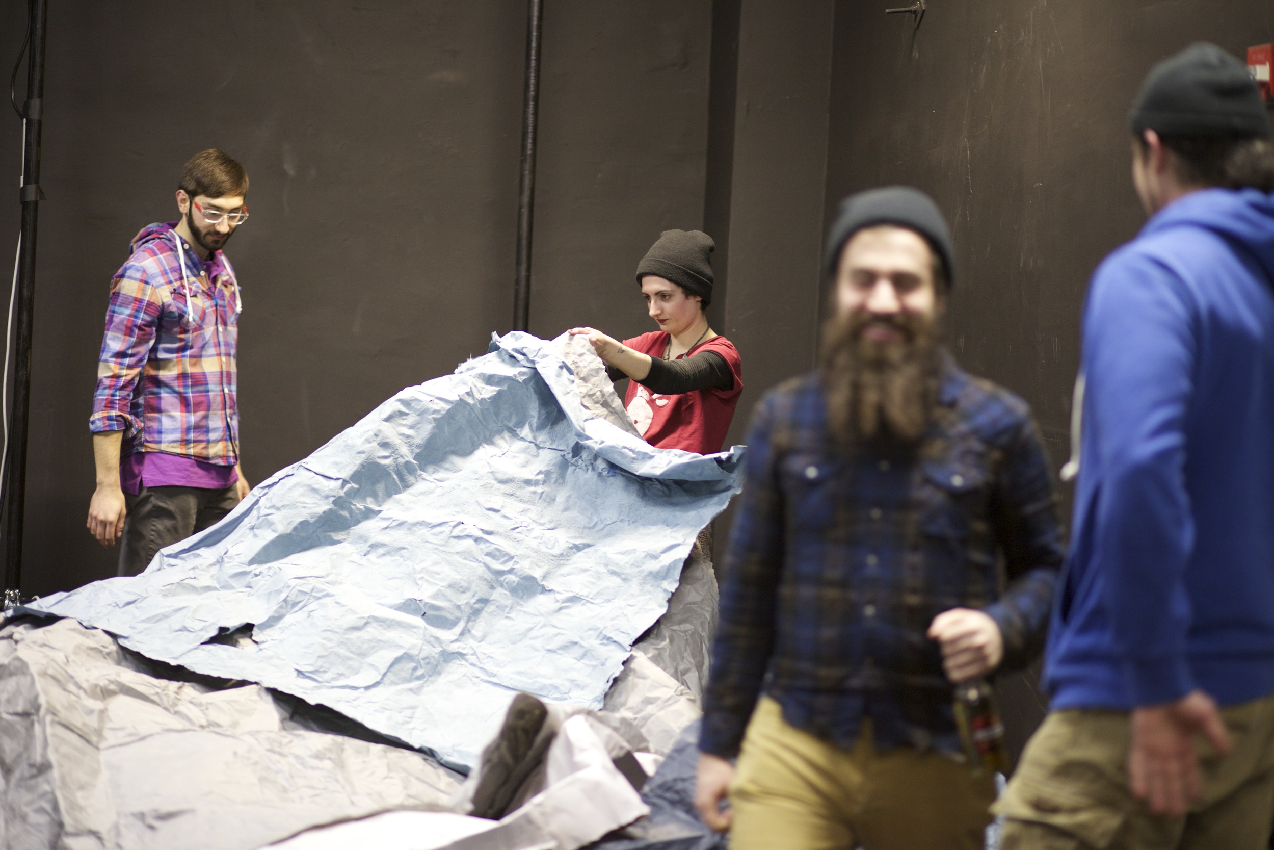 InterArts colleagues play and explore large paper.
