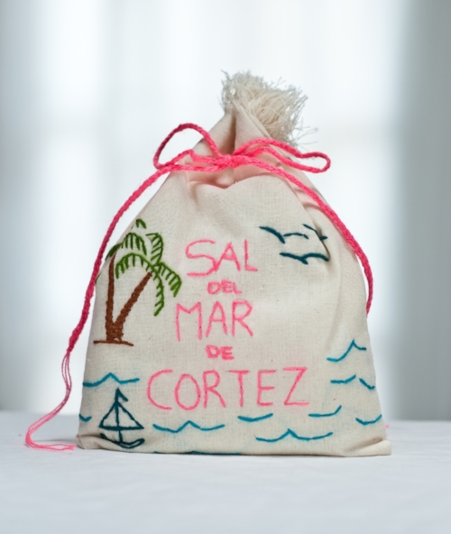 """Anyone who enjoys food will love Sal del Mar's gourmet sea salt and the rustic, intense flavor that makes it ideal for every day cooking. Harvested from the Sea of Cortez, it is a coarse moist salt that offers a healthier and cruncher experience.  AND it's already """"wrapped"""" in a hand-embroidered bag crafted by the women in a small village in Sonora, Mexico who benefit from the sale of the bags."""
