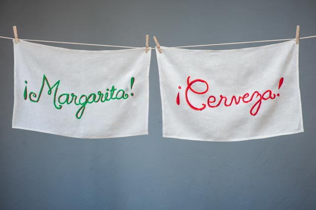 """Our hand-embroidered bar towels will bring a smile to anyone on your list who enjoys entertaining. The """"margarita"""" and """"cerveza"""" words spill across a white linen towel in vivid colors and will set the scene for any gathering. Other bar towel designs are: """"Vino,"""" """"Tequila,"""" and """"Bloody Mary."""""""