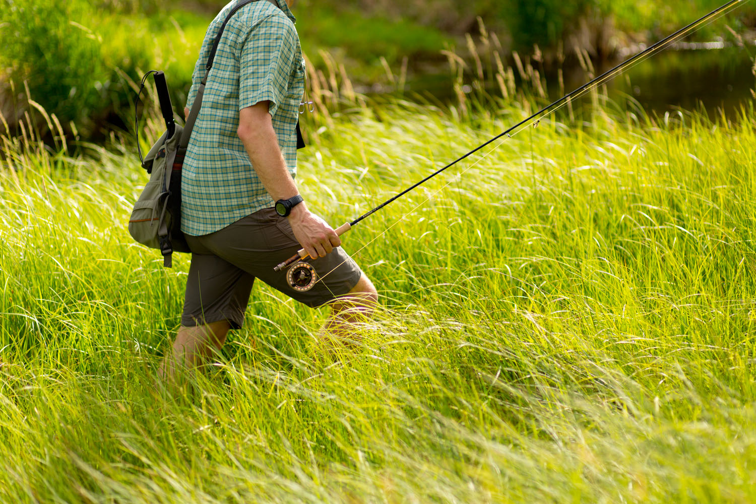 Lifestyle: Christopher Solomon walking through deep grass while fly fishing the Roaring Fork River, Carbondale, Colorado