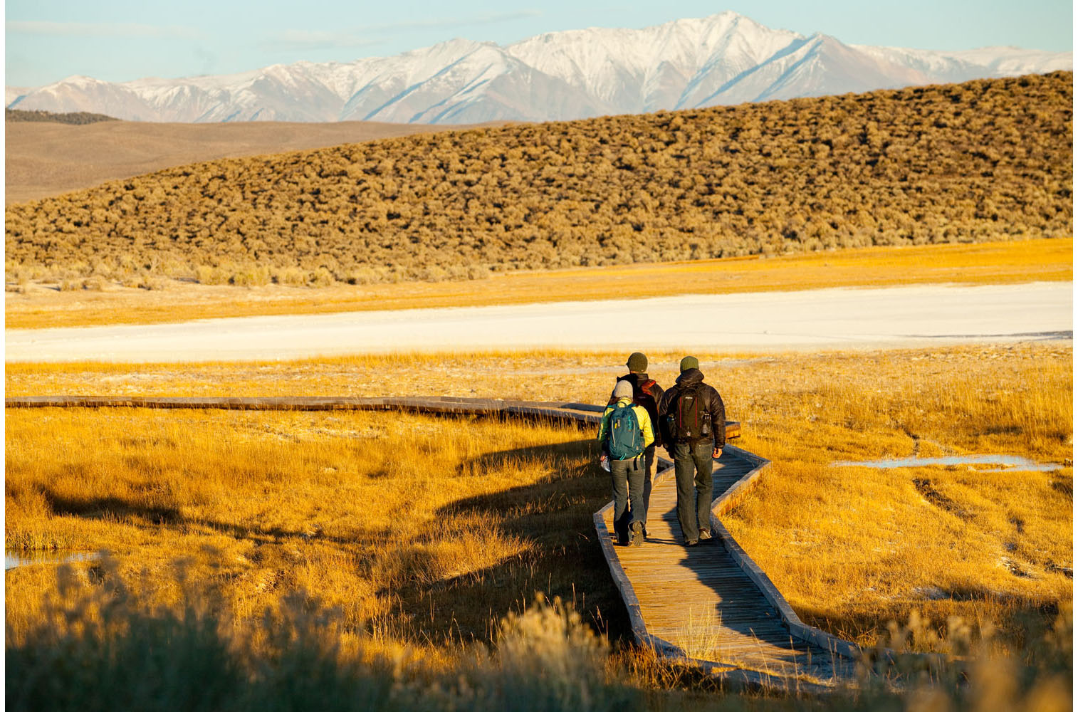 Lifestyle: Three friends walking to a natural hot springs at sunset, Owens Valley, Eastern Sierras, California