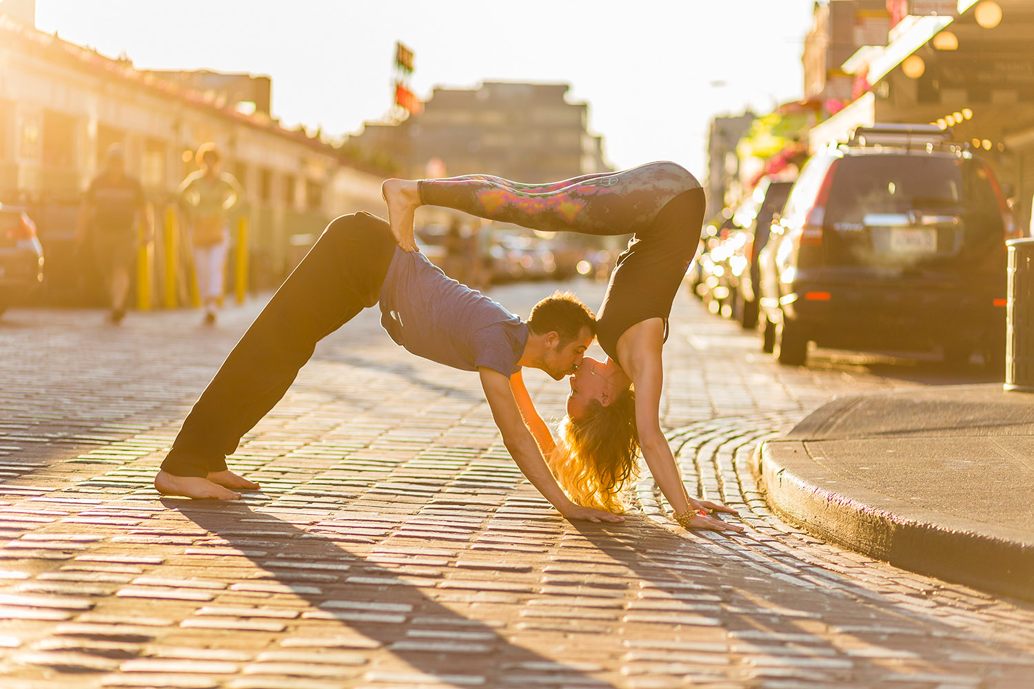 Lifestyle: Noé Khalfa and Karina Brossman practicing partners yoga at Pike Place Market in late summer light, Seattle, Washington