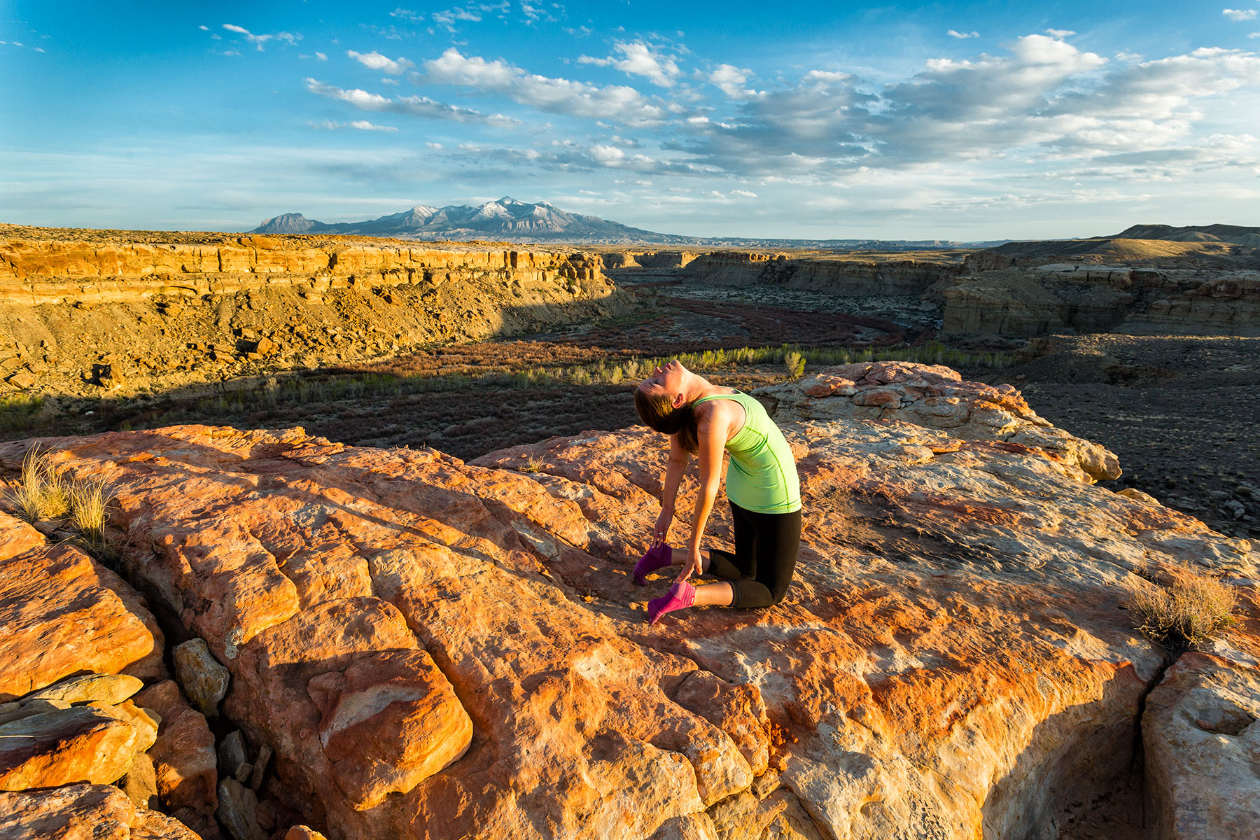 Lifestyle: Melissa Hagedorn doing yoga below the Henry Mountains at sunset, Cainville, Utah