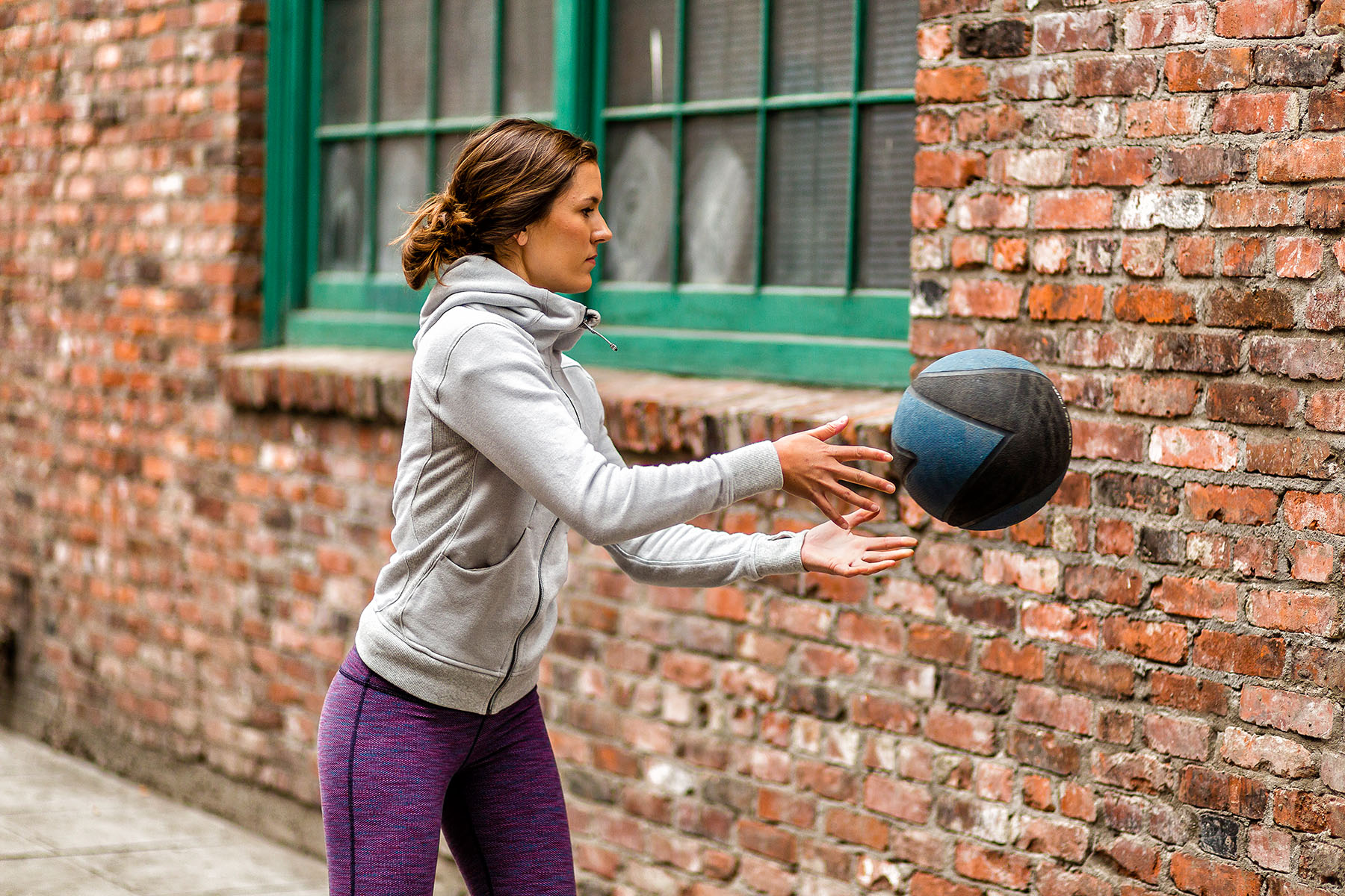 Fitness: Mary Little exercising with a medicine ball in an urban setting, Seattle, Washington