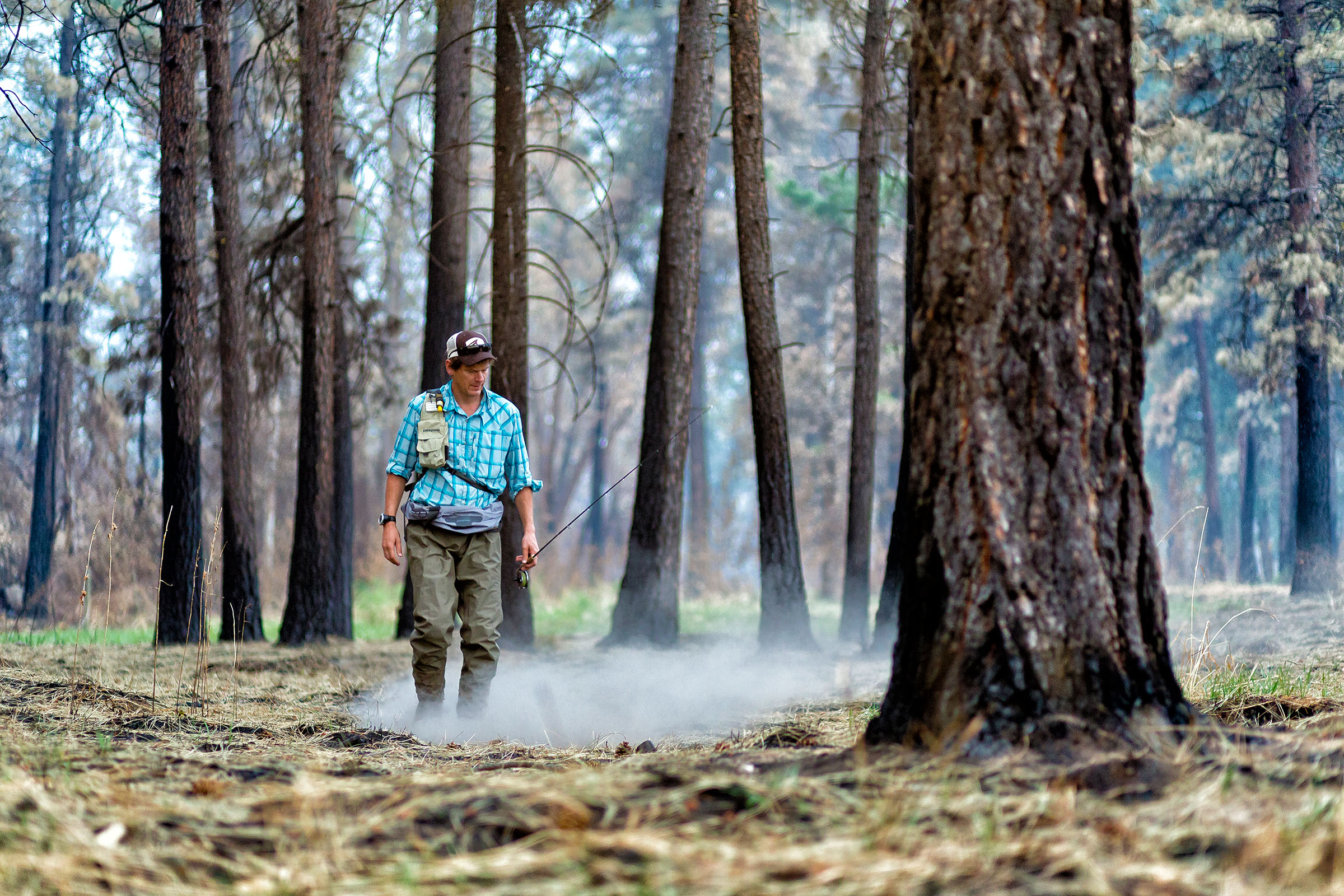 Lifestyle: Christopher Solomon walks through a recently burned forest and kicks up ash while fly fishing on the Methow River, Methow Valley, Washington