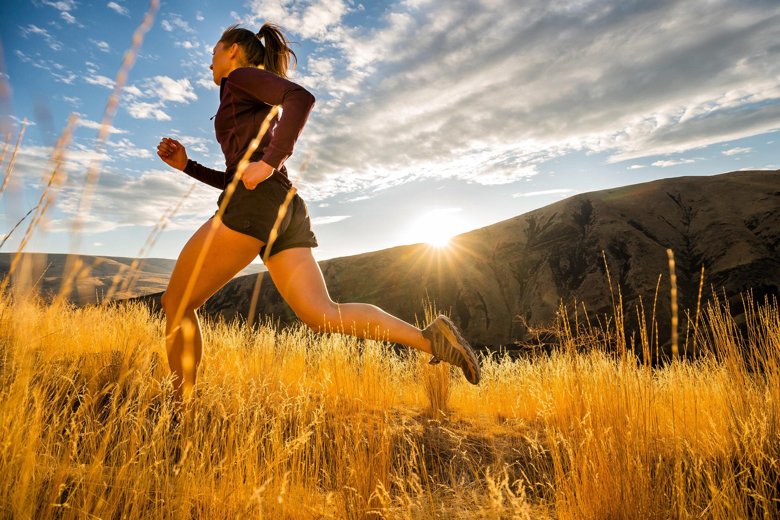 Adventure: A young woman trail running in late summer in Yakima Canyon, Washington