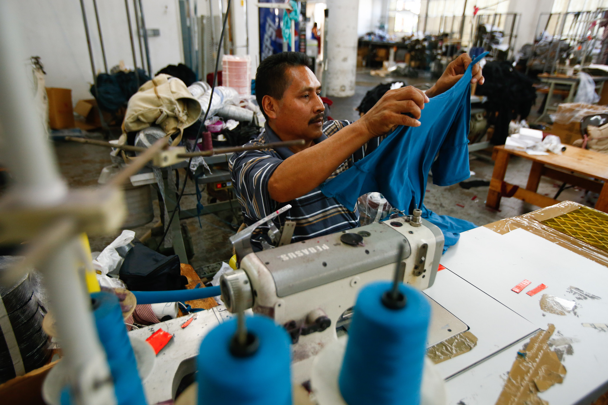 Pablo Mendez, 48, says he earns around $7 an hour as a sewing machine operator and works 11-hour days. (Claire Hannah Collins / Los Angeles Times)