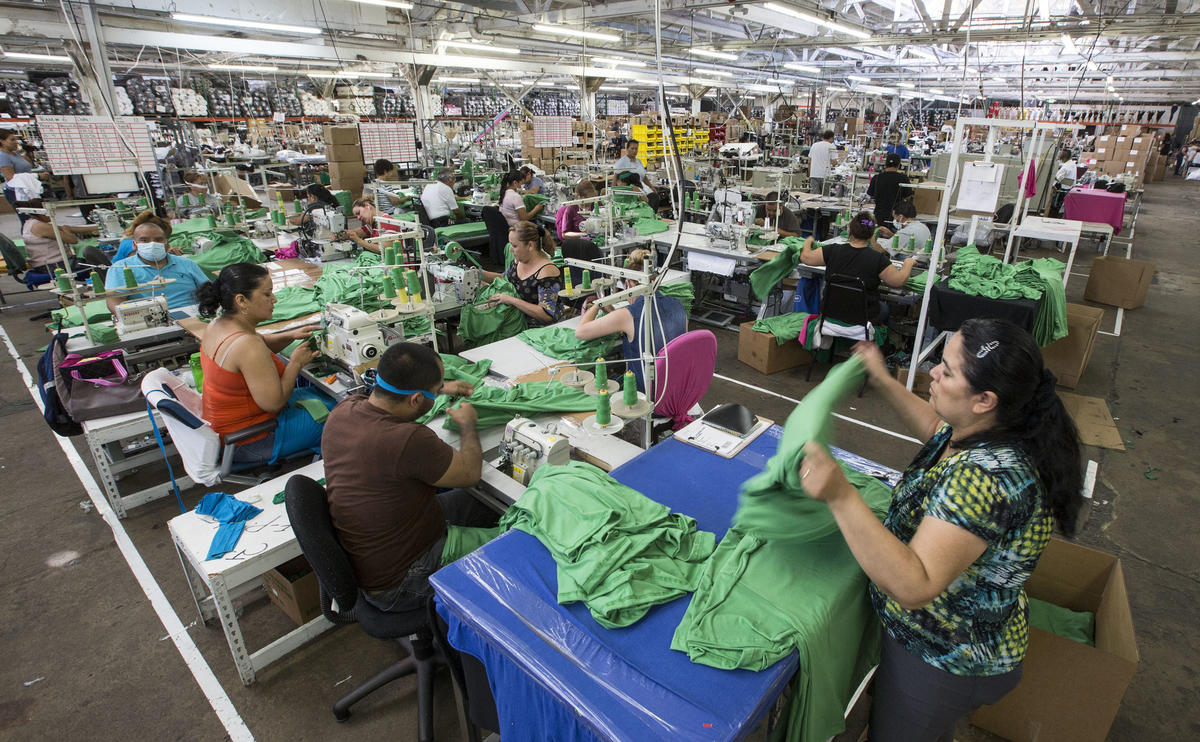 Workers inside Los Angeles Apparel, the latest incarnation of Dov Charney's clothing company. (Brian van der Brug / Los Angeles Times)