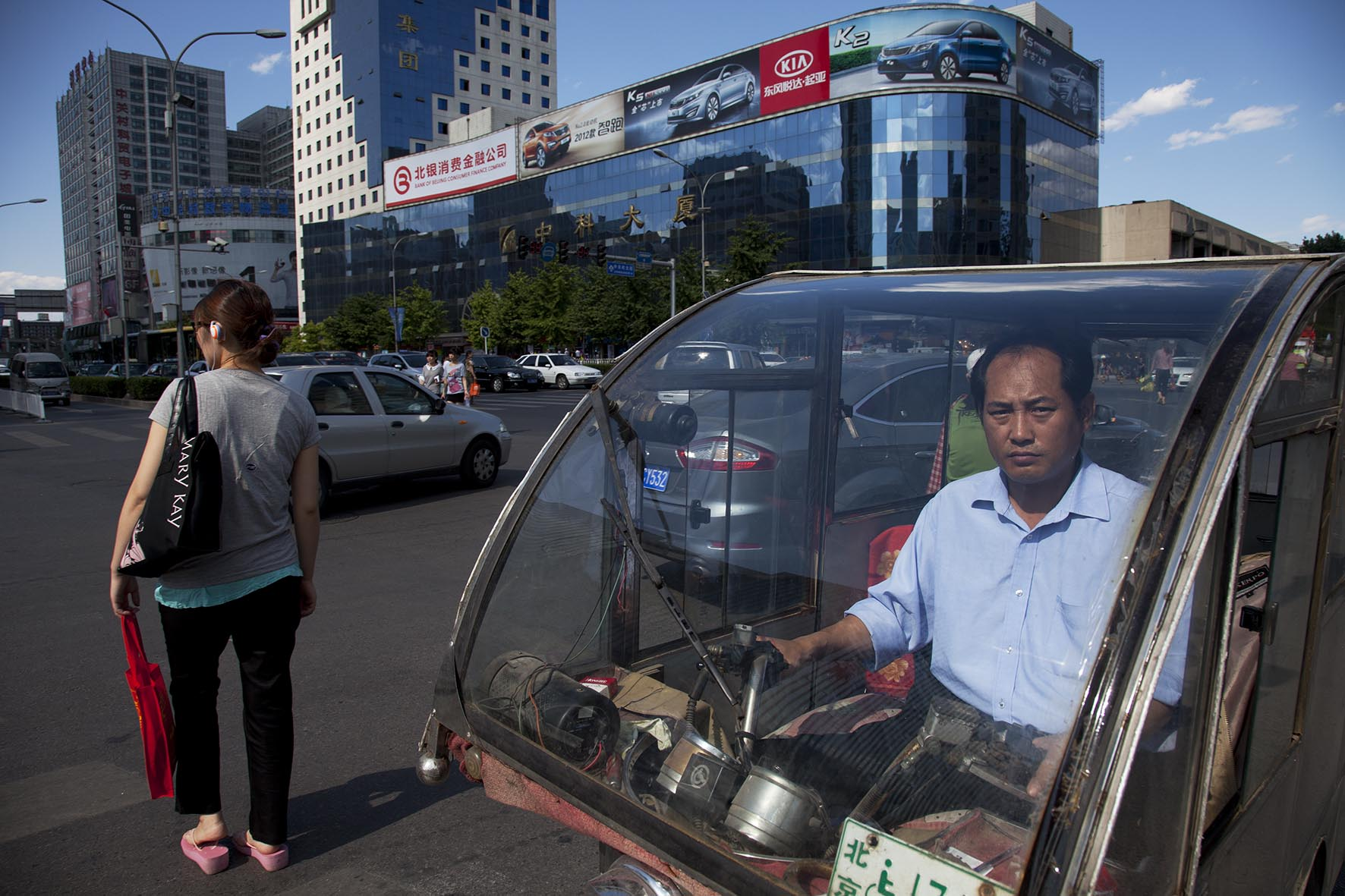 Transport worker passing the shopping malls and offices in Zhongguancun.