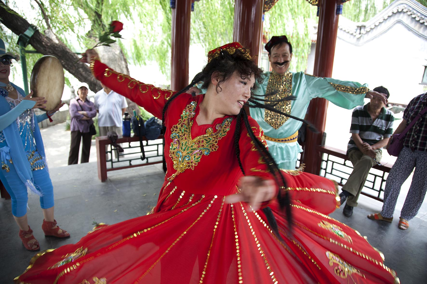 People dressed in traditional clothing dance together in a form which also tells a story in Beihai Park.