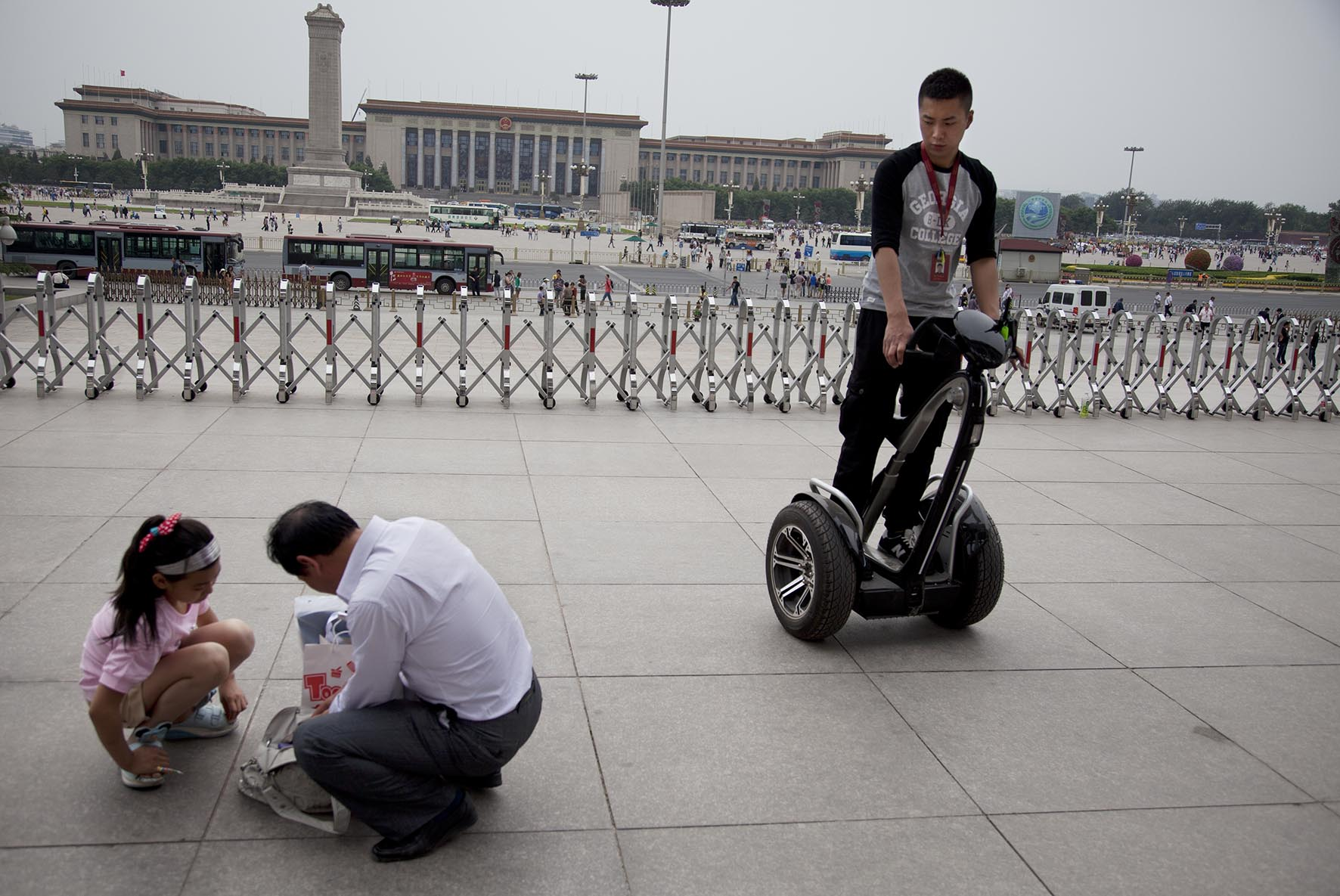 Man policing the public on a Segway two wheeled vehicle outside The National Museum of China.