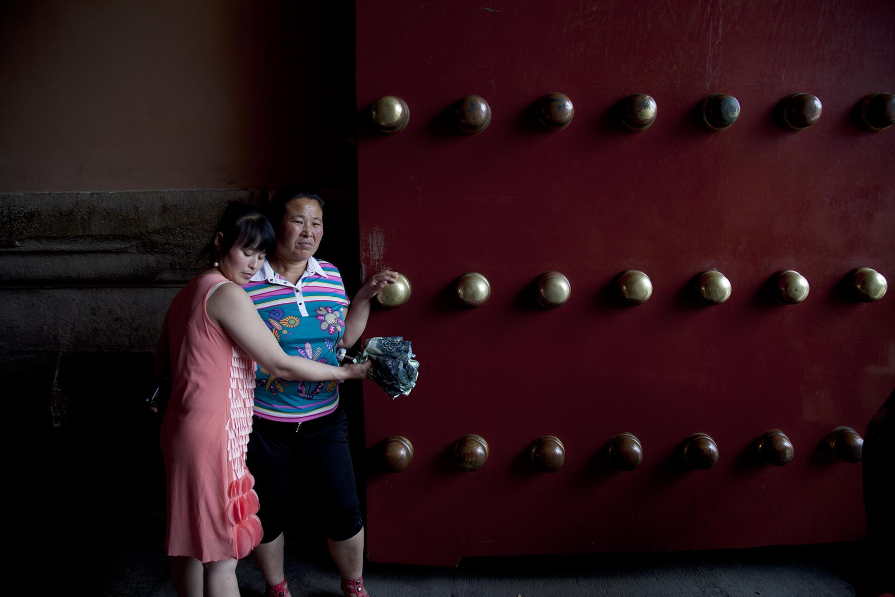 Chinese tourist hugs her mother as she touches the large brass studs on one of the doors inside The Forbidden City.