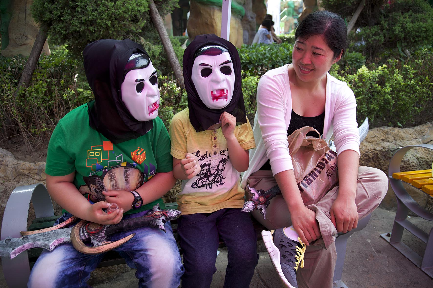 Two children wearing scary dracula horror masks. Happy Valley Beijing is an amusement park.