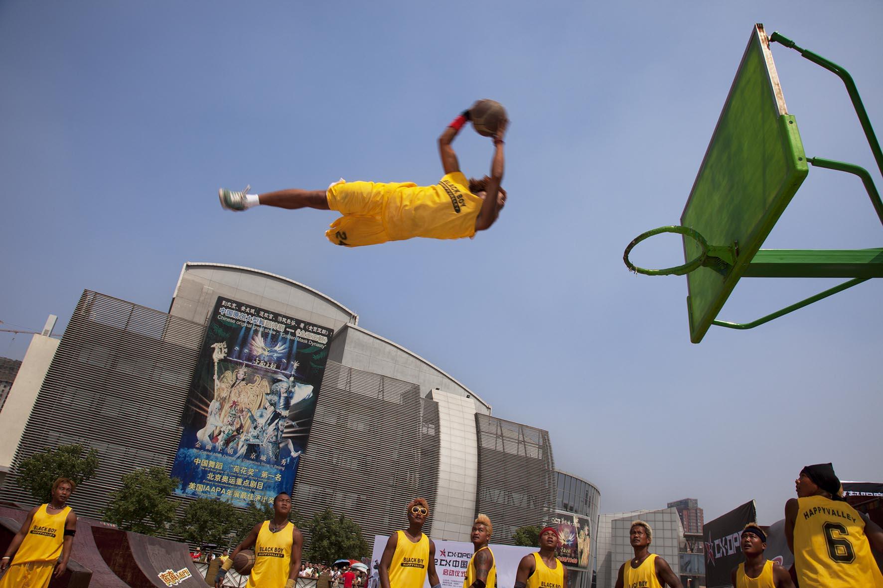 Basketball tricks team perform their slam dunk tricksat Happy Valley amusement park.