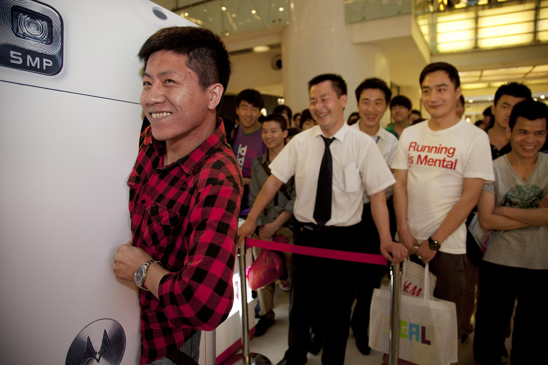 Man squeezes through a large model Motorola cell phone in order to win a handset. Skinny winners at Joy City shopping mall.