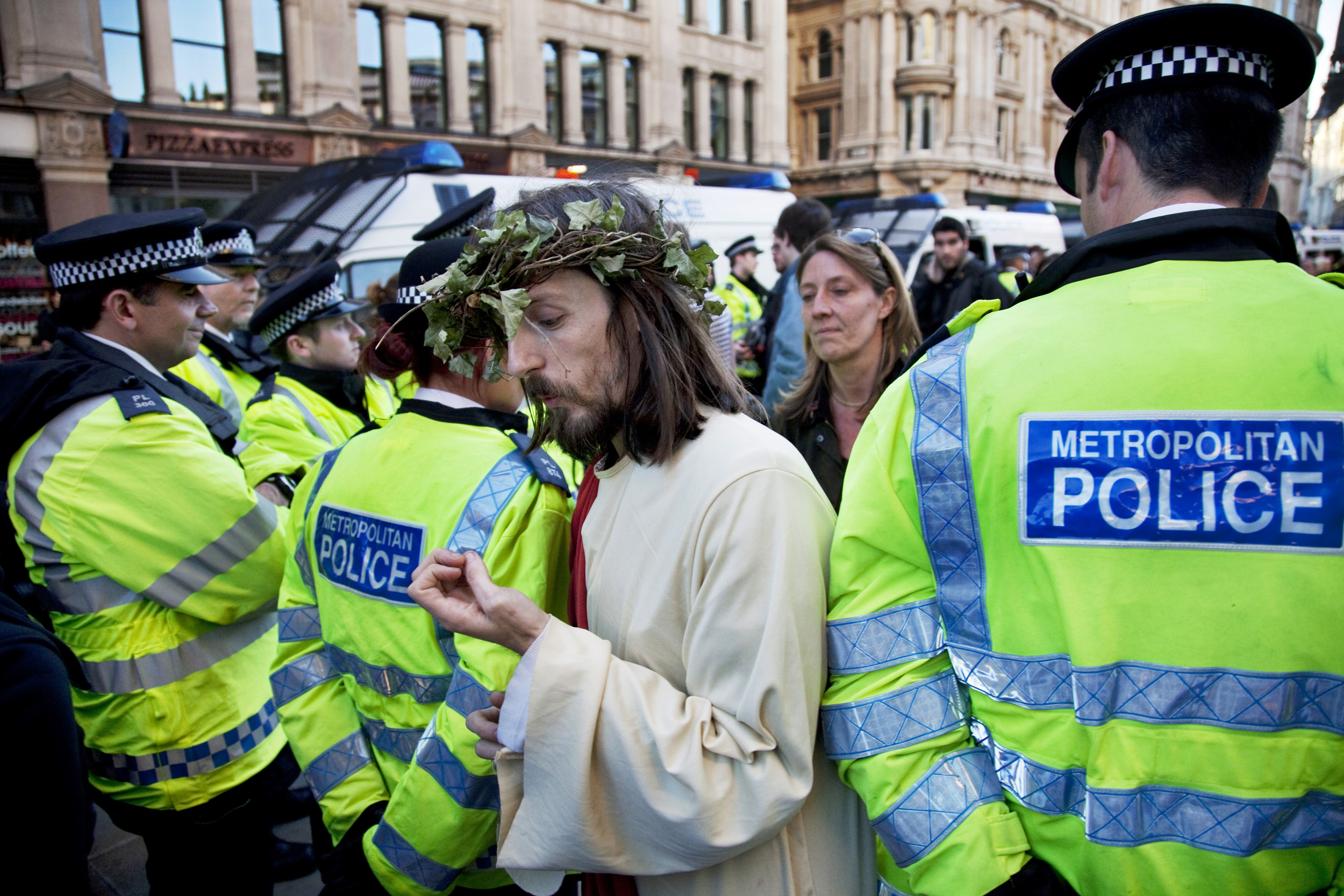 As Jesus walks through police lines at the Occupy London protest, he checks his nails.