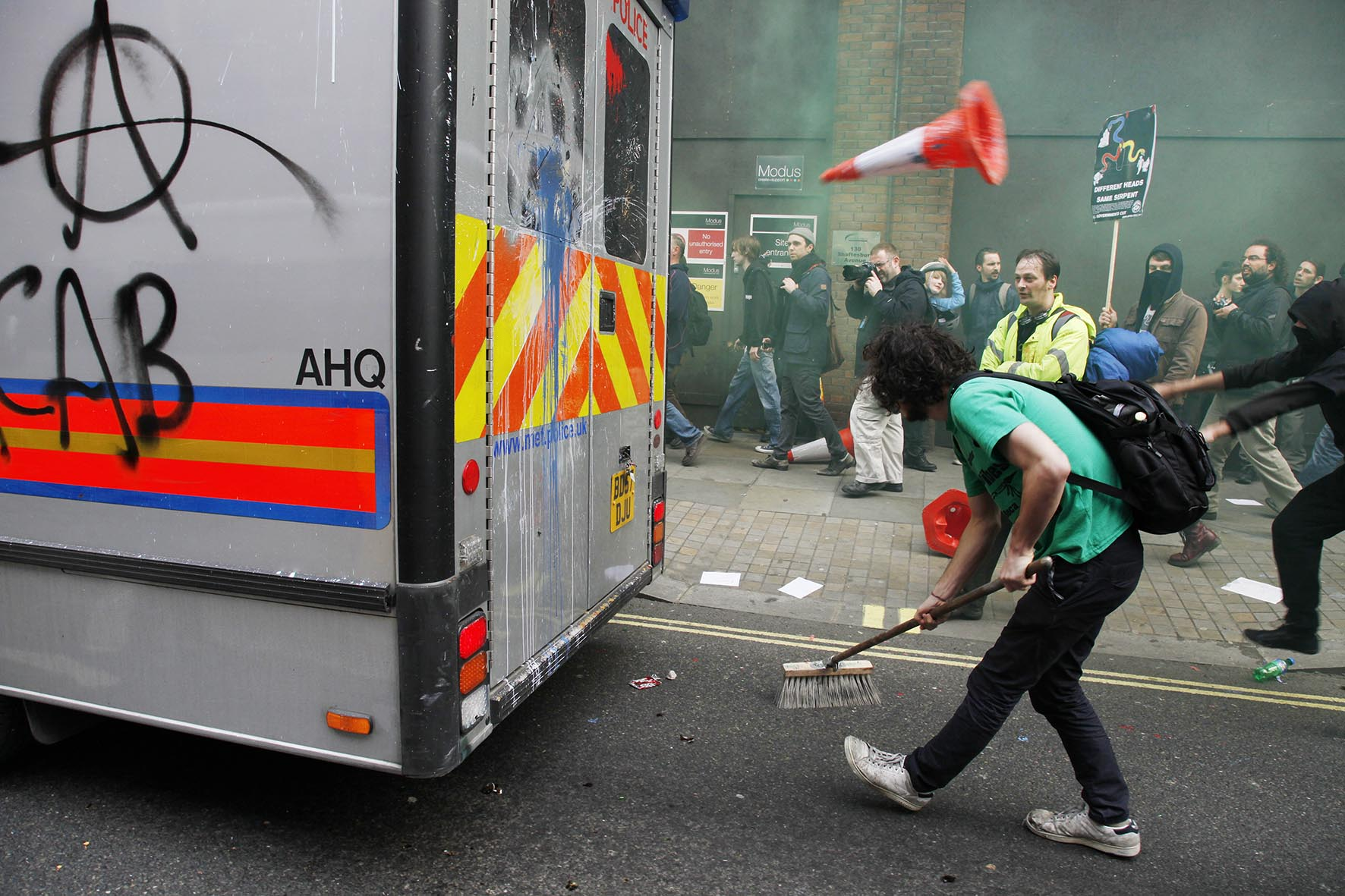 Protester pretending to sweep up during an attack on a police vehicle as anti capitalists go on the rampage through central London.