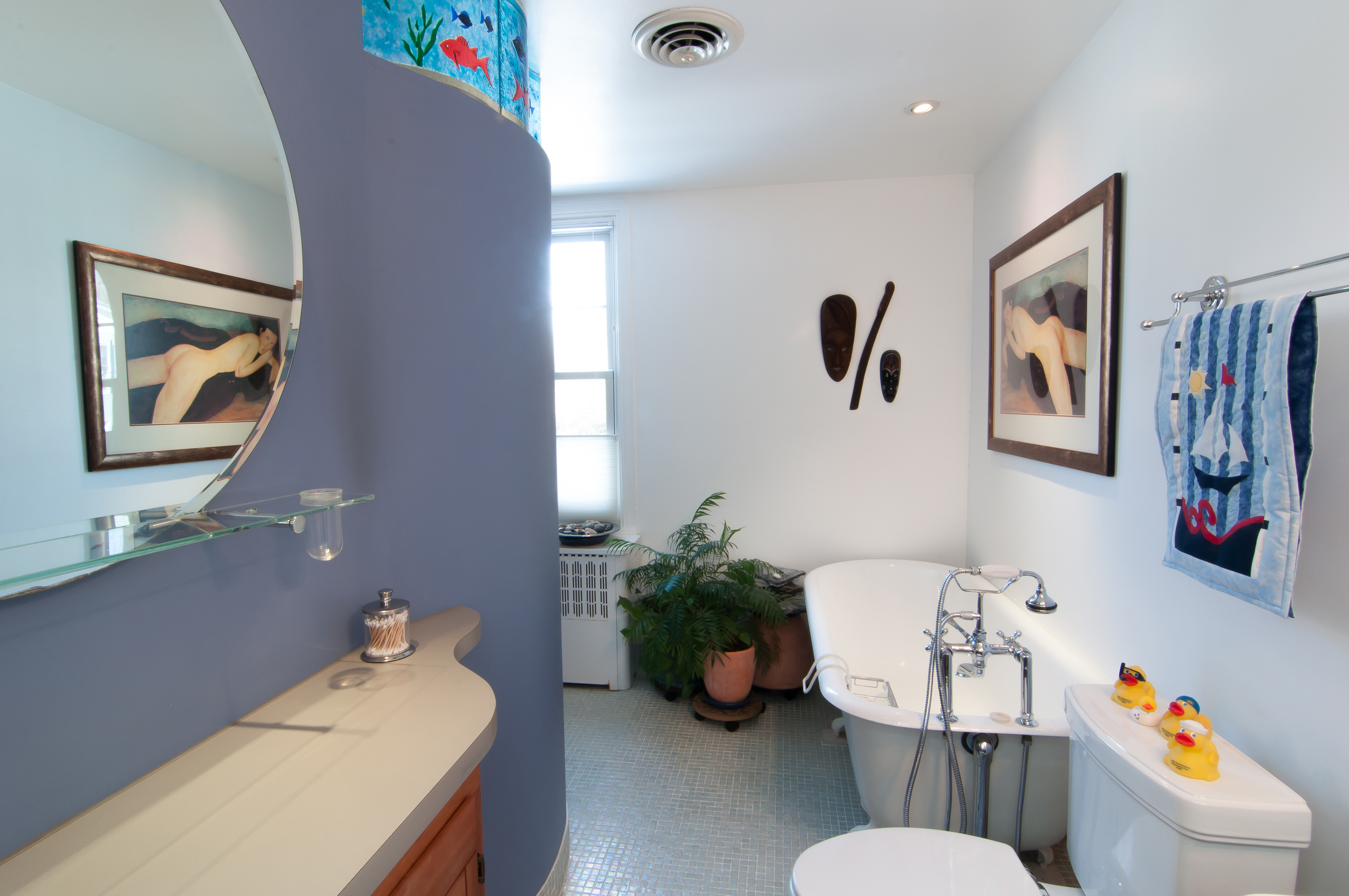 The Master bathroom with a walk in shower, claw foot tub, and farm-style sink.