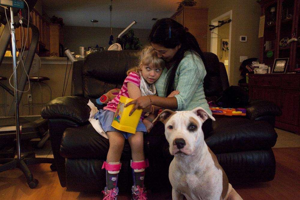 Christina cuddles with Angie, her caregiver, and her dog Bella. Jacksonville, FL