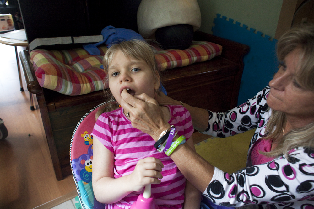 Anneliese Clark gives her daughter Christina one dose of medical cannabis concentrate infused with coconut oil, by spraying two times into her mouth. Jacksonville, FL
